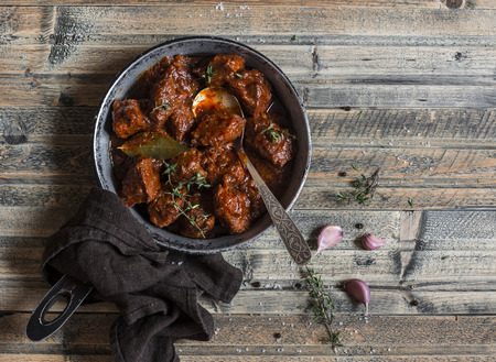 Braised beef in a frying pan on a wooden table. Top view Archivio Fotografico