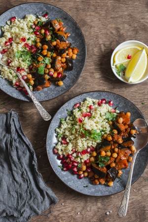 Moroccan aubergine and chickpea stew and bulgur. Healthy vegetarian lunch. On a wooden table, top view. Flat lay 版權商用圖片