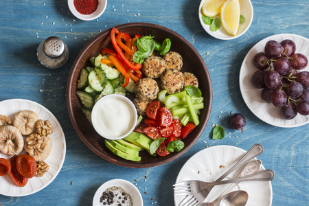 Vegetarian snack table - quinoa meatballs, fresh raw vegetables, grapes, dried fruits on wooden table, top view. Flat lay Imagens