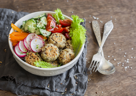 Quinoa meatballs and vegetable salad. Buddha bowl on a wooden table, top view.  Healthy, diet, vegetarian food concept. Flat lay Stock Photo