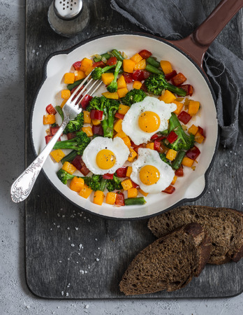 Fried quail eggs and vegetables - healthy breakfast or snack. On a wooden table, top view Zdjęcie Seryjne