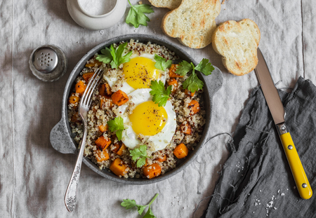 breakfast bowl: Roasted sweet potato, quinoa and fried egg bowl. Delicious healthy breakfast or lunch. Top view
