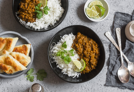 Cream coconut lentil curry with rice and naan bread - vegetarian lunch. Top view, flat lay. Vegetarian healthy food concept