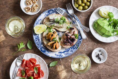Delicious tapas - sandwiches sardines, mussels, octopus, grape, olives, tomato,avocado and white wine on wooden table, top view. Flat lay