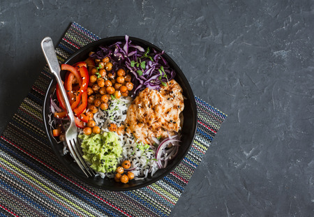 Grilled chicken, rice, spicy chickpeas, avocado mash, cabbage, pepper buddha bowl on dark background, top view. Delicious balanced food concept Archivio Fotografico
