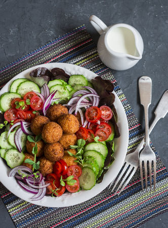 Falafel and vegetables salad. Delicious vegetarian food concept. Buddha bowl on dark background, top view