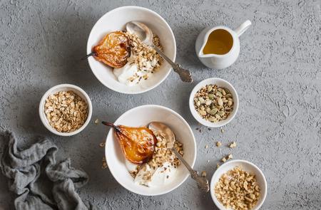 Peras cocidas caramelizadas con el yogur y el granola griegos en un fondo gris, visión superior. Desayuno saludable. Lay Flat
