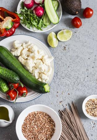Vegetarian food. Zucchini, cauliflower, sweet pepper, soba noodles, buckwheat, avocado, tomatoes  - healthy vegetarian food. On a gray background, top view Stock Photo