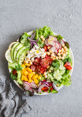 Spring vegetable buddha bowl. Salad with veggies, chickpeas, avocado and feta. Delicious healthy food.  On a gray background, top view