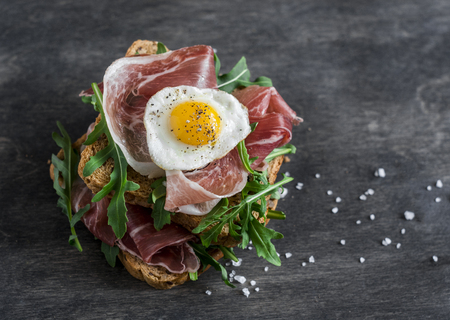 Prosciutto, arugula, and fried quail eggs sandwich on wooden background, top view. Delicious breakfast, snack or appetizer