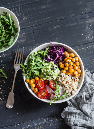 Quinoa and spicy chickpea vegetable vegetarian buddha bowl. Healthy food concept. On a dark background, top view 写真素材