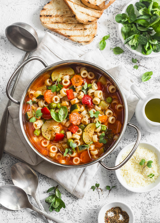 Minestrone soup in a pan on a light table, top view. Delicious vegetarian food concept. Flat lay