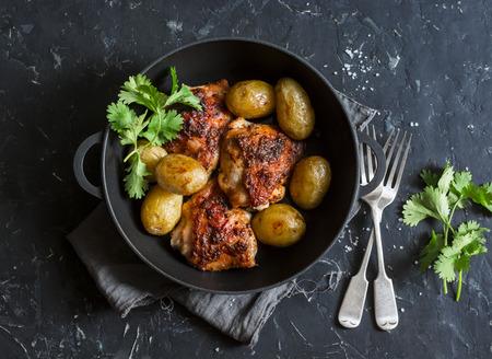 Een pot gebakken harissa kip en nieuwe aardappelen op een donkere achtergrond, bovenaanzicht Stockfoto