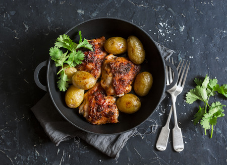 One pot baked harissa chicken and new potatoes on a dark background, top view