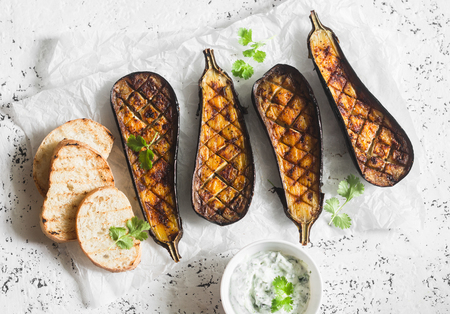 Grilled eggplant and sauce tzatziki on a light background, top view. Baked aubergine