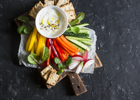 sesame cracker: Healthy snack - raw vegetables and yogurt sauce on a wooden cutting board, on a dark background, top view. Vegetarian healthy food concept