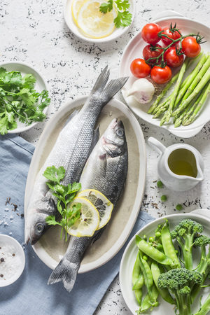 Set of healthy balanced ingredients for lunch - sea bass, asparagus, tomatoes, broccoli, green peas, olive oil and spices. On a light background, top view. Flat lay