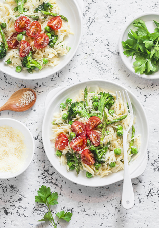 Asparagus, broccoli, green peas, cream orzo pasta with tomatoes and parmesan cheese. Delicious healthy food in a mediterranean style on a light background, top view Stock Photo