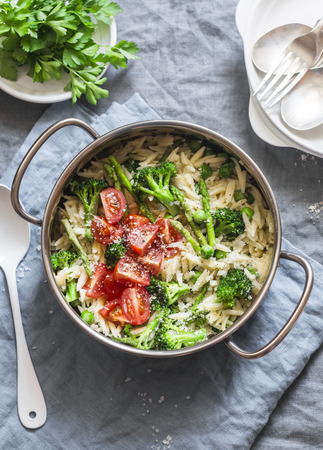 One pot orzo primavera. Orzo pasta with asparagus, broccoli, green peas and cream in a saucepan. On a light background, top view Stock Photo