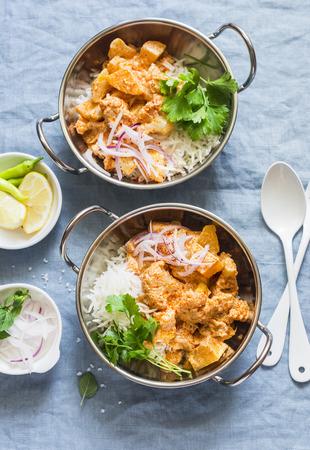 채식 감자와 콜리 플라워 카레 요리에 쌀과 파란색 배경, 상위 뷰. 채식 건강 식품 개념입니다. 평평한 평지
