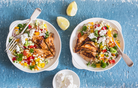 Yogurt marinated grilled chicken breast and israeli couscous and vegetables tabouli salad on a blue background, top view