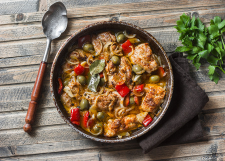 Slow cooker chicken with olives and sweet peppers in the pan on wooden background, top view. Comfort food