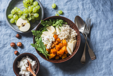 Full bowl with baked sweet potatoes, barley, arugula and apples. Vegetarian buddha bowl with autumn vegetables and grains, on a blue background, top view Stock Photo
