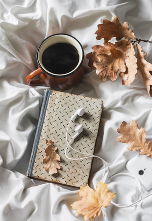 Coffee, book, headphones, phone on the bed, top view. Leisure, cozy home concept. Warm autumn mood