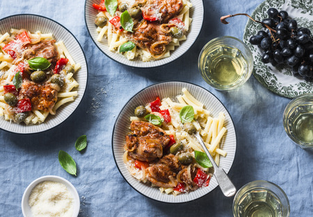 Italian food table. Pasta with slow cooker chicken with olives and sweet peppers, white wine. On a blue background, top view Stock Photo