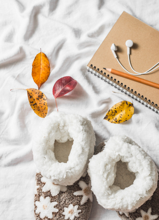 Soft home uggs, notepad, headphones, autumn leaves - lazy cozy home weekend. On a light background, top view