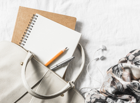 Womens leather handbag, clean blank notepad, pen and scarf on a light background, top view. Free space for text