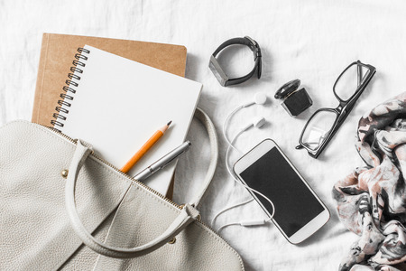 Womens leather handbag, clean blank notepad, pen, glasses, smartphone, earphone, watch, perfume, scarf on a light background, top view. Free space for text. Woman workplace business background Archivio Fotografico