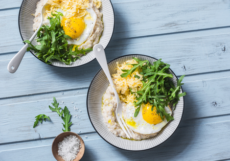 Cheese savoury oatmeal with fried egg and arugula on a blue background, top view. Healthy balanced breakfast food