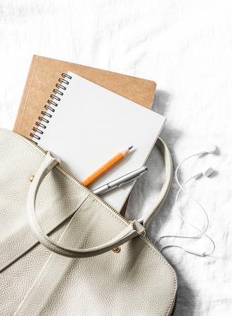 여성 가죽 핸드백, 깨끗 한 빈 메모장, 밝은 배경, 상위 뷰 펜. 텍스트를위한 여유 공간