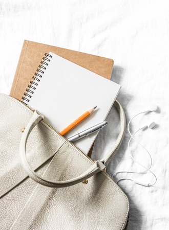 Womens leather handbag, clean blank notepad, pen on a light background, top view. Free space for text Archivio Fotografico