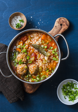 Multi grain, meatballs and vegetables soup in a pot on a blue background, top view. Comfort home cooking healthy seasonal food concept