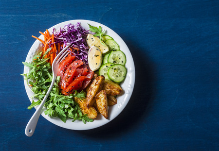 Smoked salmon, baked potatoes, vegetables buddha power bowl on blue background, top view. Red cabbage, carrots, arugula, potatoes, smoked salmon fish bowl. Healthy food concept