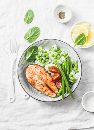 Healthy balanced meal lunch plate - baked salmon with rice and vegetables on a light background, top view. Stockfoto