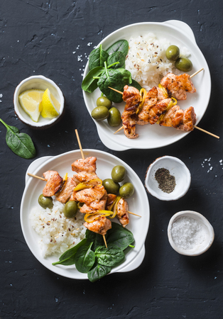 Salmon skewers, olives, spinach, rice - healthy lunch table. Grilled salmon fish skewer and side dish on a dark background, top view
