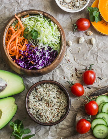 Healthy vegetarian food set background. Cabbage salad, avocado, tomatoes, cucumbers, pumpkin, wild rice on a paper background, top view. Flat lay Stock Photo