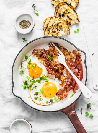 Traditional breakfast or snack - fried eggs, bacon, grilled bread on light background, top view. Flat lay