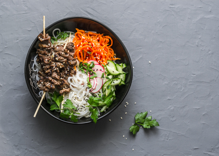 Power balanced buddha bowl. Asian style beef skewers, rice vermicelli, pickled vegetables salad carrots, cucumbers, radishes, herbs on grey background, top view. Free space for text recept Stock fotó