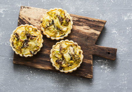 Savory hands pie with porcini mushrooms, leeks, potatoes on a cutting board on a grey background, top view Stock Photo