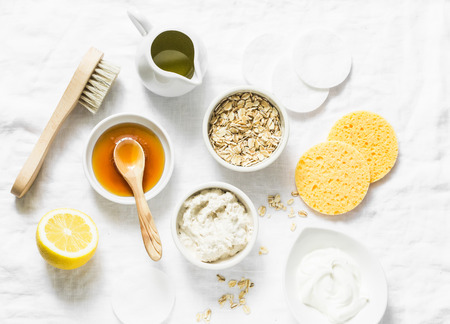 Natural moisturizing, nourishing, cleansing face mask - coconut oil, oatmeal, natural yogurt, vitamin E, honey, face brush, sponge on light background, top view. Flat lay, beauty products