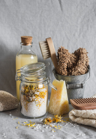 Bath accessories - homemade sea salt with calendula, natural shampoo, brush, washcloth, pumice, homemade oat soap. Health, beauty concept. Flat lay