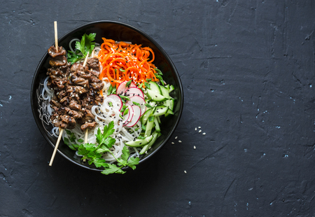 Beef skewers, rice vermicelli, pickled vegetables salad carrots, cucumbers, radishes, herbs on dark background, top view. Free space for text. Power balanced buddha bowl
