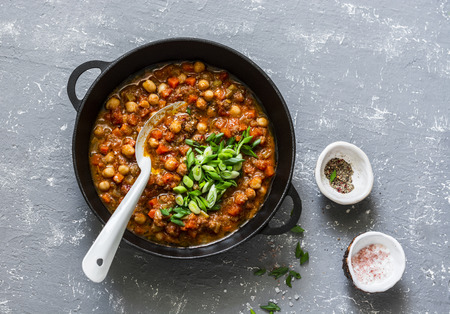 Vegetarian buffalo chickpea chili with mushrooms in a pan on a gray background, top view. Healthy vegetarian food concept Stock Photo