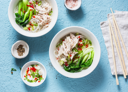 Asian style soup. Rice noodles, boiled chicken, vegetables and broth - delicious diet lunch on blue background, top view. Flat lay