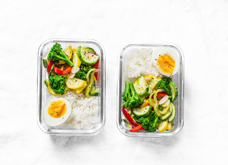 Vegetarian lunch box - stewed vegetables, rice and boiled egg on a light background, top view. Health food concept