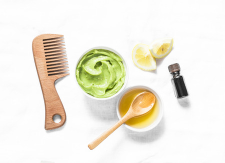 Avocado, honey hair homemade mask on light background, top view. Natural products for hair health and beauty